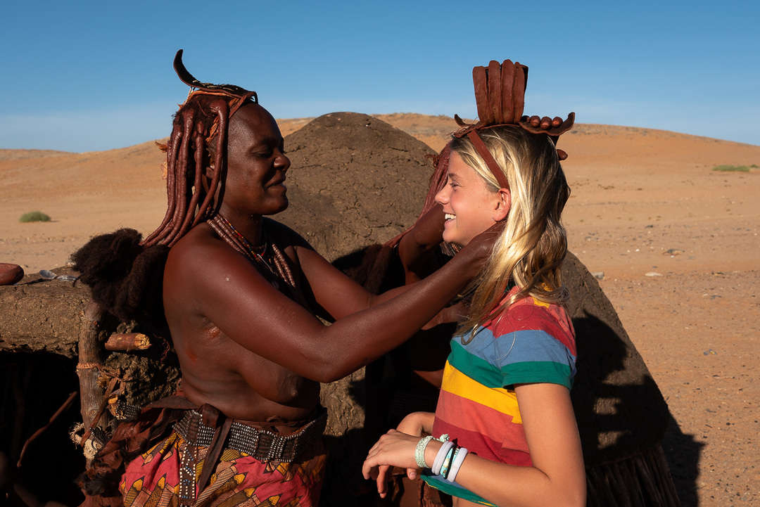 HImba lady putting necklace on visitor