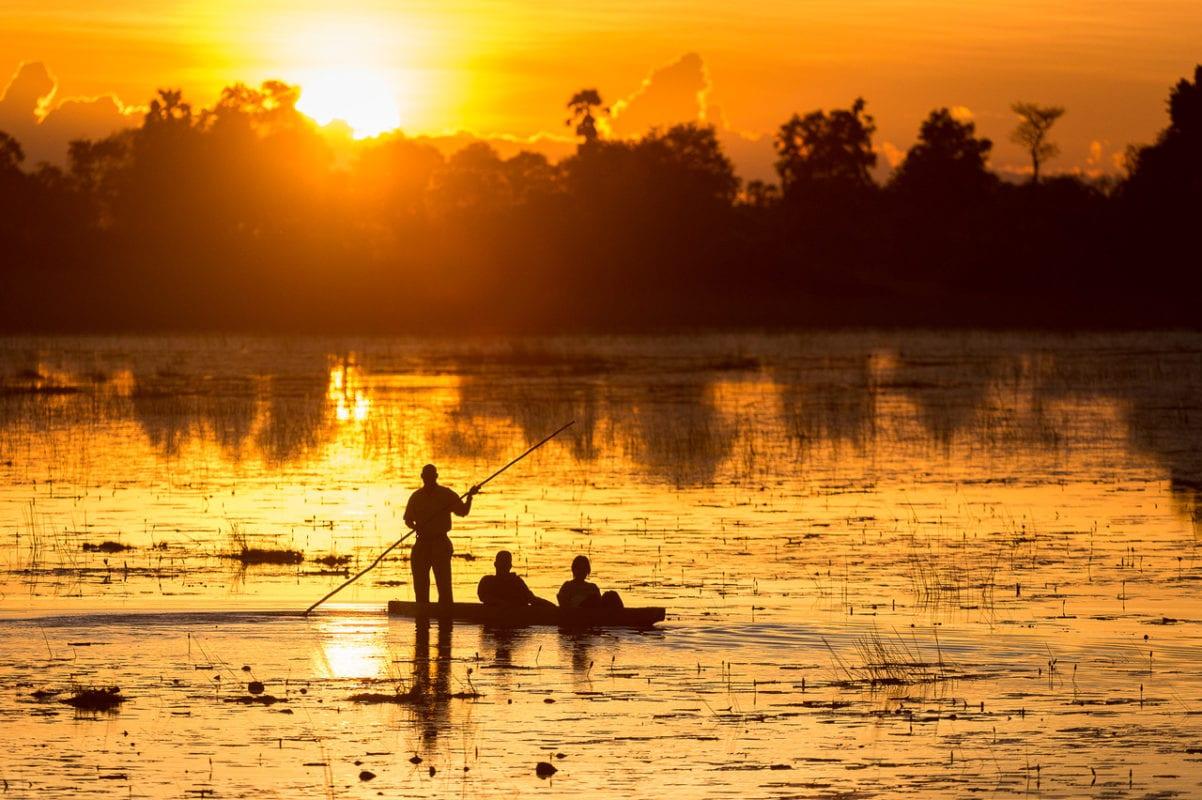Bright orange sunset behind couple in a mokoro - Okavango Delta