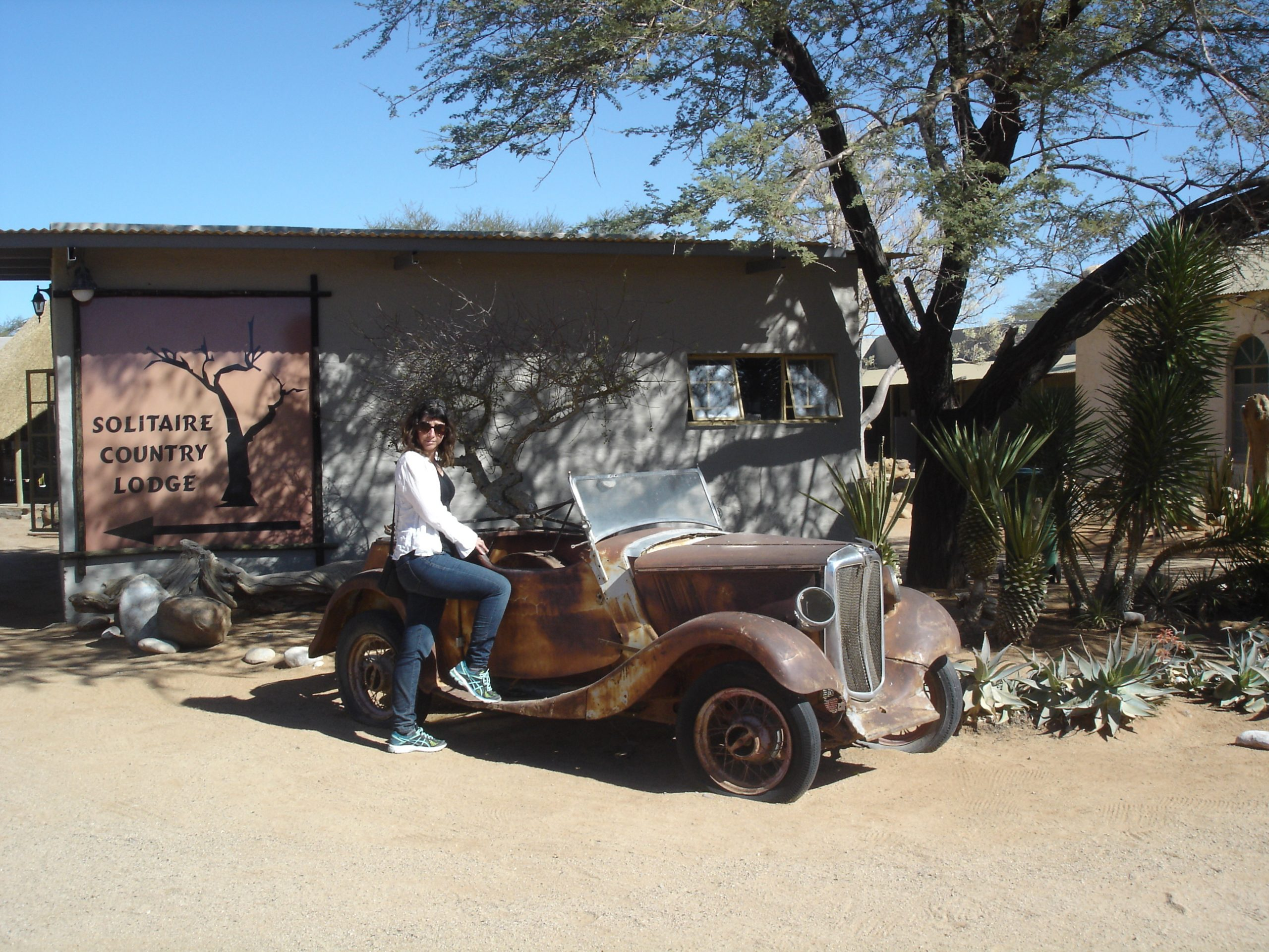 Natalie posing with a old ford our side the Solitaire Country Club Namibia
