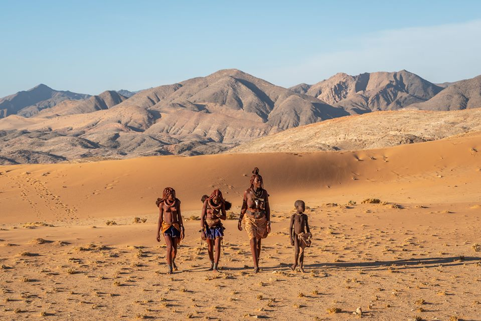 Himba lady and three young girls walking in the desert